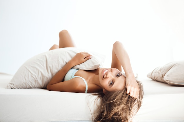 Young beautiful woman lying on bed early in morning