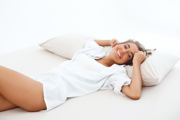 Young beautiful woman lying on bed early in morning.