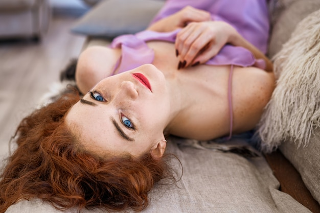 Young beautiful woman lying on bed
