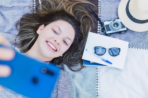 Молодая красивая женщина, лежа принимая селфи.