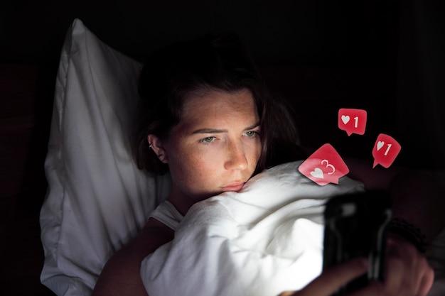 私のソーシャルメディアでいいねやコメントを受け取るスマートフォンでベッドに横たわっている若い美しい女性...