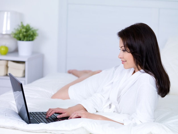 Молодая красивая женщина, лежа на кровати и используя ноутбук