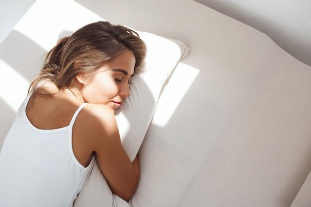 이른 아침에 침대에 누워 젊은 아름 다운 여자