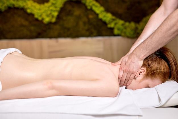 Молодая красивая женщина, лежа на массажном столе и наслаждаясь массажем от профессионала