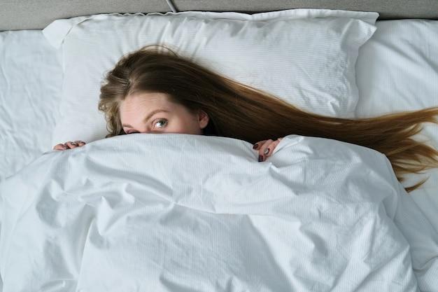 Молодая красивая женщина, лежа на подушке в постели
