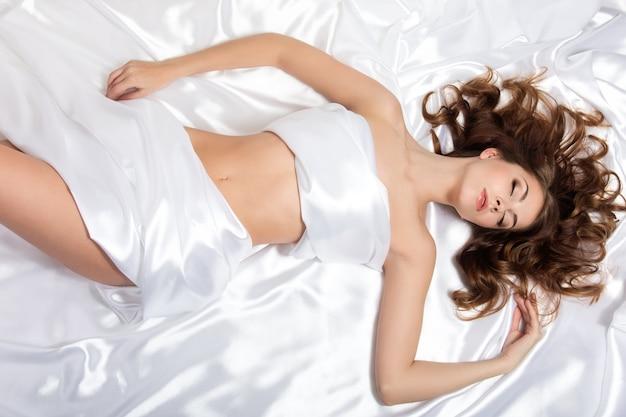 白い絹の上に横たわる若い美しい女性