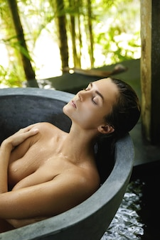 Young and beautiful woman lying and relaxing in the stone bathtub