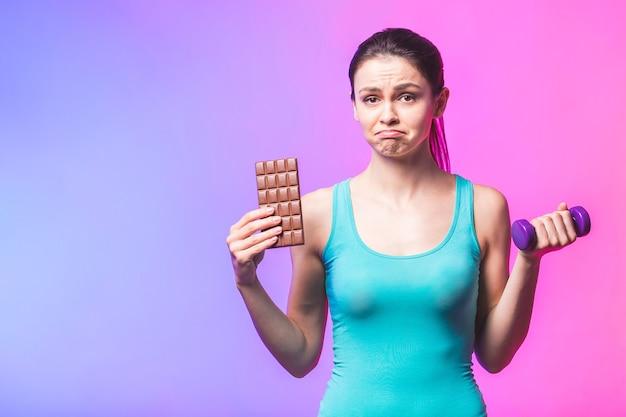 スポーツと不健康な食品の間で選択を行う若い美しい女性