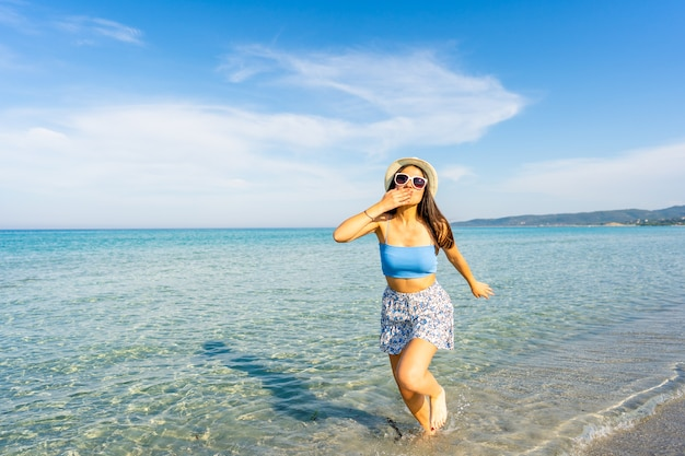 Молодая красивая женщина делает жест поцелуя с рукой в рот, гуляя в морской воде