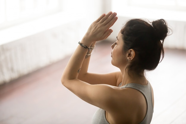 Young beautiful woman making namaste gesture, loft studio