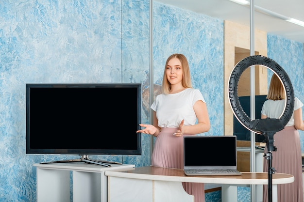 Young beautiful woman making presentation with monitor and laptop empty display template blank screen template for tv and laptop presenter of online stream with ring lamp teacher online education