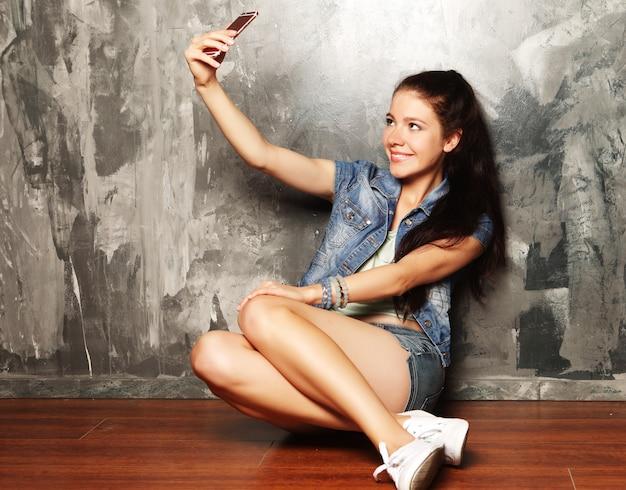 Young beautiful woman making selfie photo on smartphone