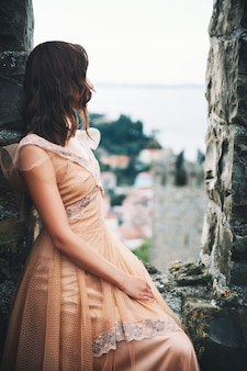 Young beautiful woman in medieval dress on the historical european streets of old town