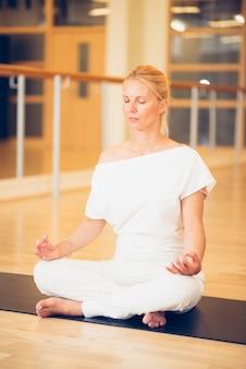 スタジオで床に座っている蓮の中で瞑想する若い美しい女性