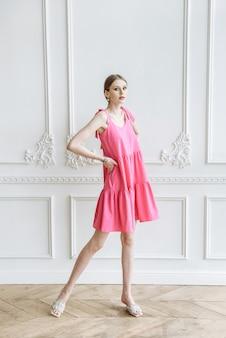 스튜디오 의류 카탈로그에서 분홍색 드레스를 입고 포즈를 취하는 젊은 아름다운 여성 모델
