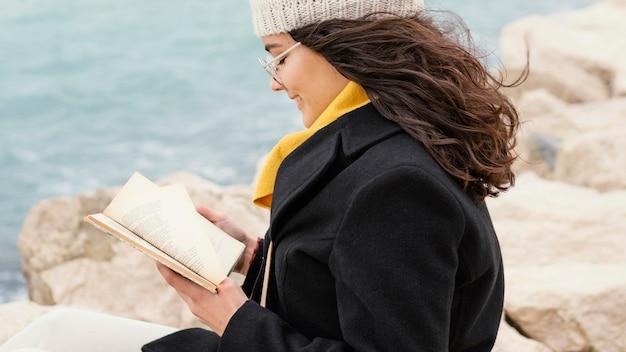 Giovane bella donna nel libro di lettura della natura