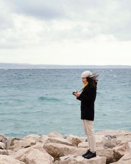 Giovane bella donna in natura con la fotocamera