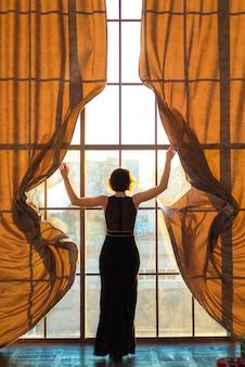 Молодая красивая женщина возле большого окна на закате
