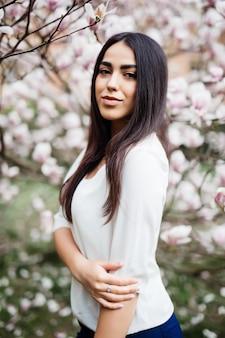 Young beautiful woman near magnolia blooming tree. cute young woman near magnolia tree