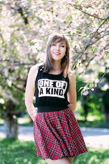 사쿠라 피 나무 근처 젊은 아름 다운 여자. 핑크 꽃, 봄, 청소년 개념. 세련 된 여자 웃 고입니다. 벚꽃 나무와 피 정원입니다. copyplace, 텍스트를위한 장소입니다.