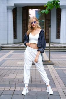 カカズ国籍の若い美しい女性は、午後に街の通りで白いトラックスーツを着て、ブルージーンズに自信を持ってサングラスをかけた金髪の女性が夏にポーズをとる