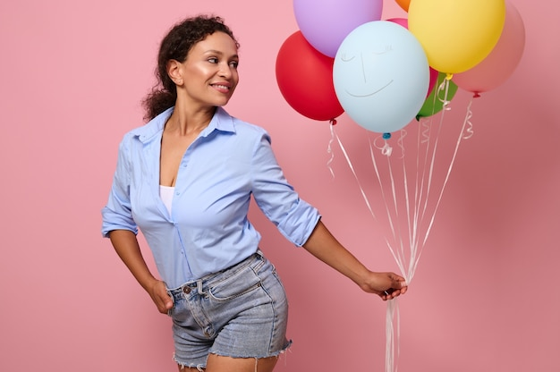 混血民族の若い美しい女性は、テキストと広告のコピースペースとピンクの背景の上に分離された彼女の手で色とりどりの明るい気球を見ています
