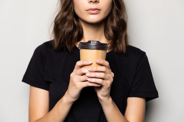 Young beautiful woman offers white cup of coffee isolated on gray wall