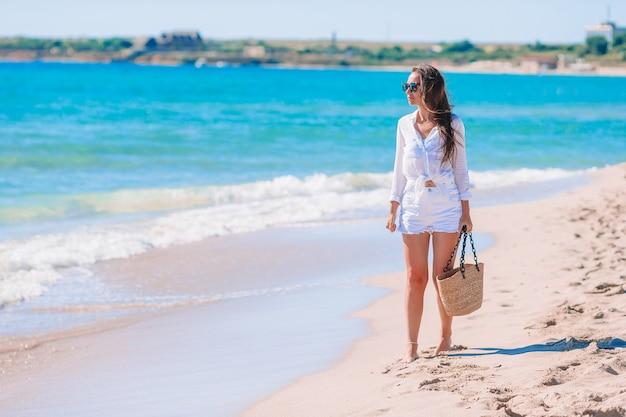 白い砂の熱帯のビーチで若い美しい女性