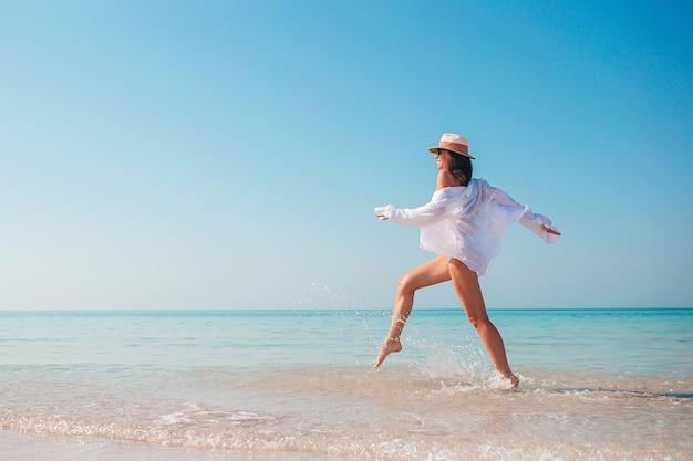 해변 휴가 튀는 및 파도에서 재생에 젊은 아름 다운 여자