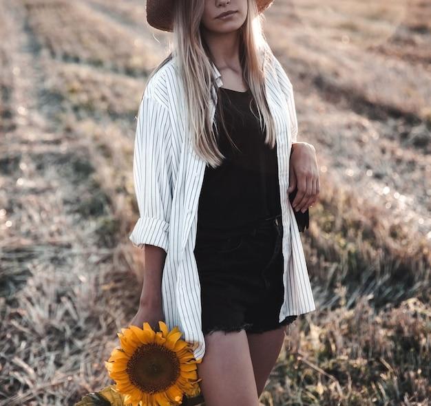 夏のフィールドで若い美しい女性