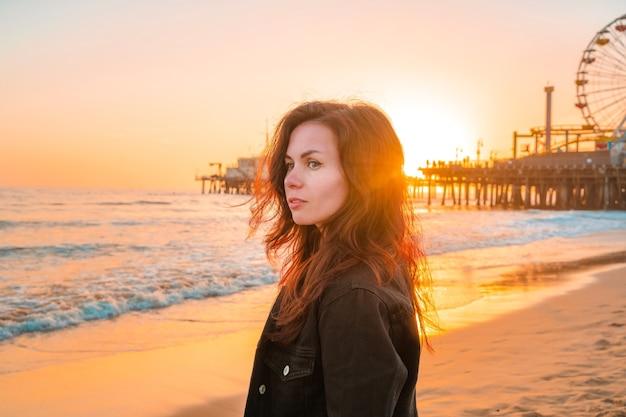 Молодая красивая женщина на пляже санта-моника перед оранжевым закатом в лос-анджелесе, калифорния