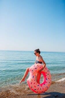 Молодая красивая женщина на пляже с ее надувным кольцом