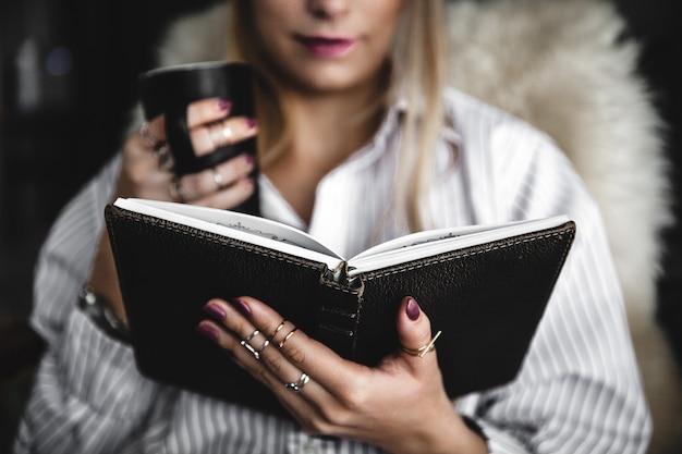 本を一杯のコーヒーを読んで床に若くてきれいな女性