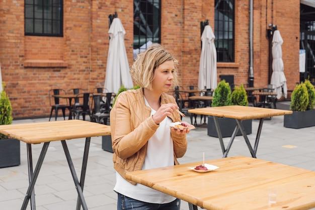 観光旅行の若い美しい女性は、ストリートカフェでベリージャムと揚げチーズを食べています。休息と楽しみ。旅行と観光。ライフスタイル。それは素晴らしい時間です。