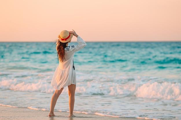 Молодая красивая женщина на тропическом пляже в закат.
