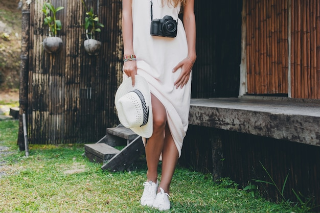 Молодая красивая женщина на тропическом отдыхе в азии, летний стиль, белое платье в стиле бохо, кроссовки, цифровая фотокамера, путешественник, соломенная шляпа, ноги крупным планом детали