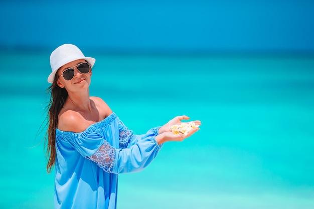 白い砂浜の熱帯のビーチで若い美しい女性。