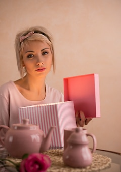 Young beautiful woman opening gift box while having tea-party