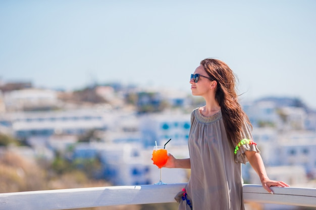 Young beautiful woman in outdoor cafe with tasty cocktail. happy tourist enjoy european holidays with amazing view of old city in greece