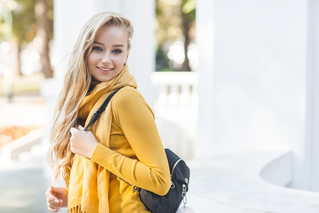 Young beautiful woman  outdoors. closeup portrait of cheerful ladyon spring or autumn background. girl with backpack.