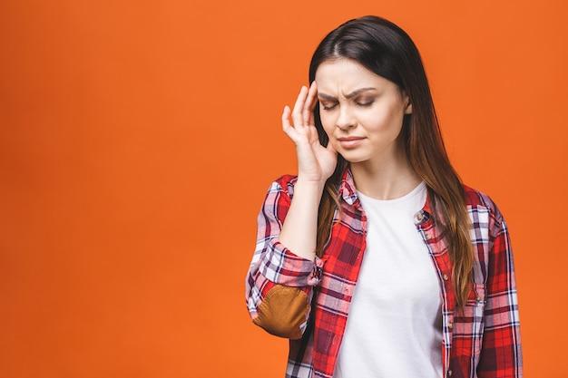 Молодая красивая женщина над изолированной оранжевой предпосылкой страдая от головной боли отчаянной и усиленной потому что боль и мигрень. руки на голову.