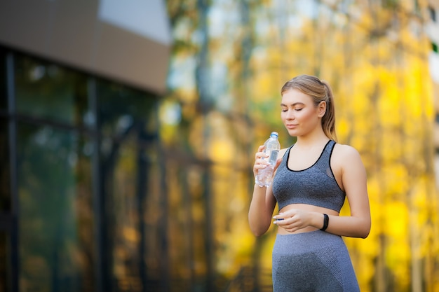 Young beautiful woman in the park wearing sportwear and drinking water