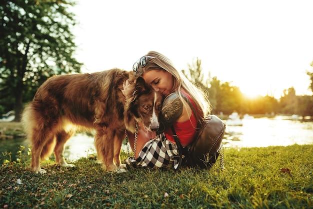 Молодая красивая женщина, лаская свою милую собаку в парке