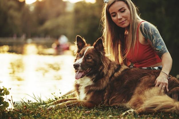 公園で彼女のかわいい犬をかわいがって若い美しい女性