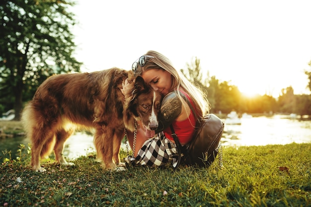 Young beautiful woman petting her cute dog in park