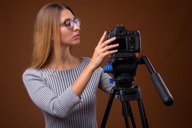 三脚でデジタル一眼レフカメラをチェックする若い美しい女性の写真家