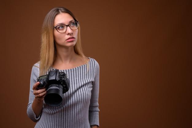 茶色の壁にデジタル一眼レフカメラを保持している若い美しい女性の写真家