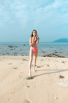 Young beautiful woman in a pink bathing suit stands on a sandy beach