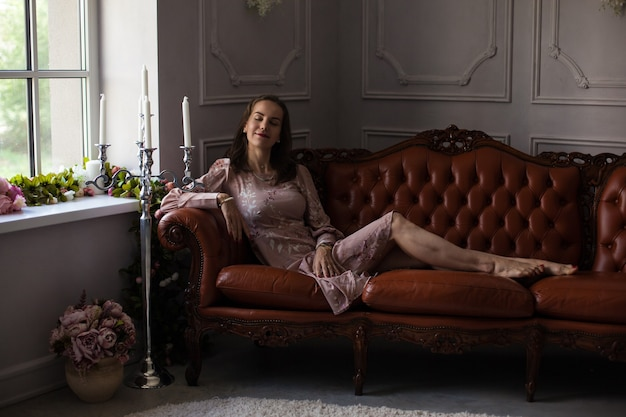 Young beautiful woman in pink dress sits on brown leather sofa