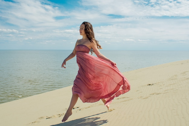 A young beautiful woman in a pink dress walks on the sand dunes